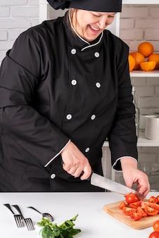 Vista frontale del cuoco unico femminile che taglia i pomodori a pezzi