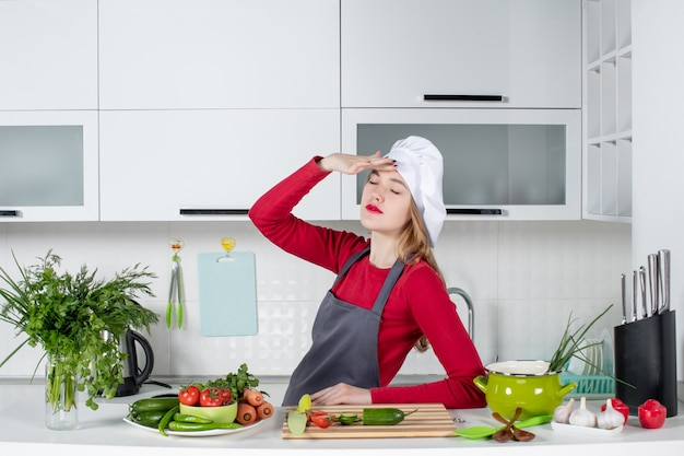Front view female chef in cook hat closing eyes