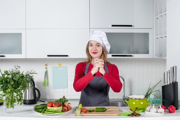 Front view female chef in cook hat holding hands together