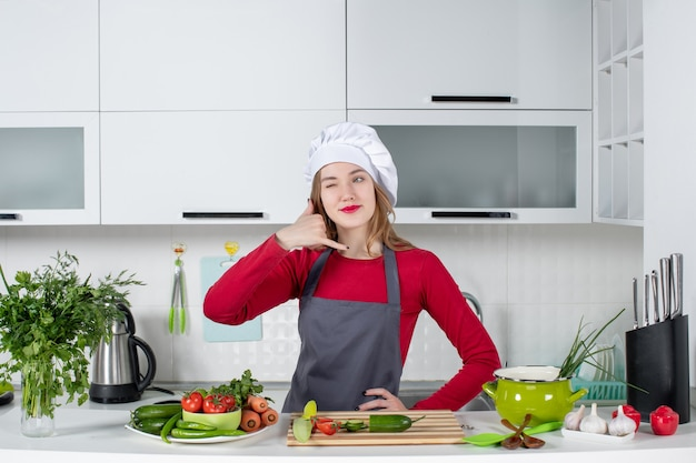 Front view female chef in cook hat making call me gesture