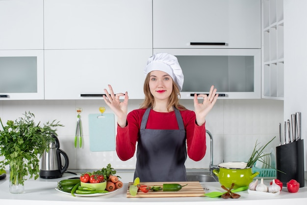 Front view female chef in cook hat making okey sign