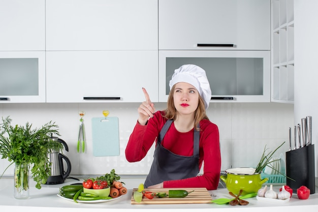 Front view female chef in cook hat pointing finger something