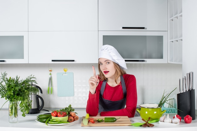 Front view female chef in cook hat pointing finger up