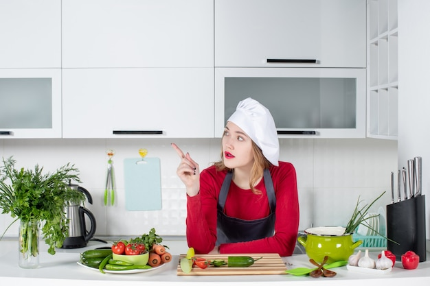 Front view female chef in cook hat pointing at left in kitchen