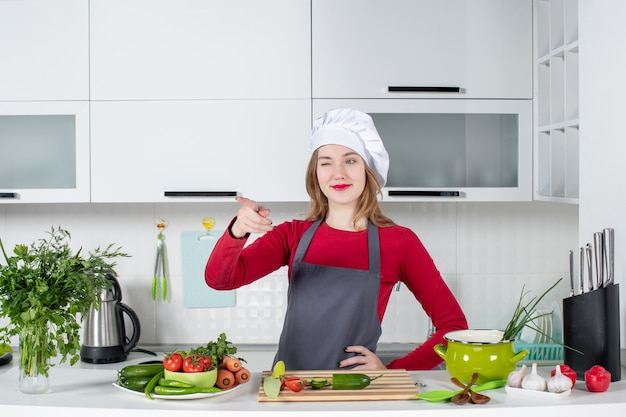 Front view female chef in cook hat pointing with finger pointing at front