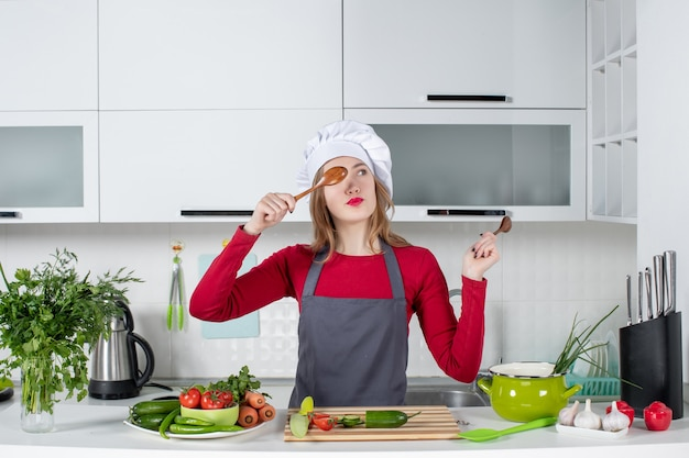 Front view female chef in cook hat putting wooden spoon in front of her eye