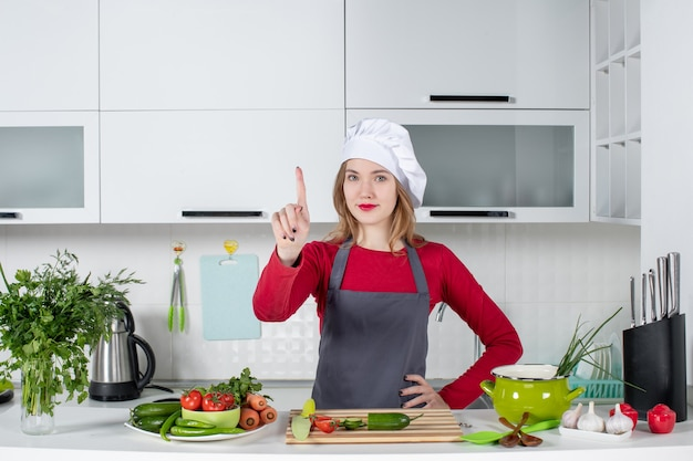 Front view female chef in cook hat showing point finger
