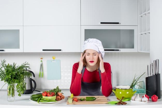 Cuoco unico femminile di vista frontale in cappello del cuoco con gli occhi chiusi che tengono la sua testa