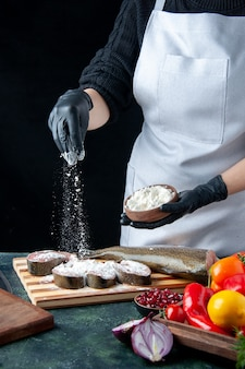 Front view female chef covering raw fish slices with flour on kitchen table