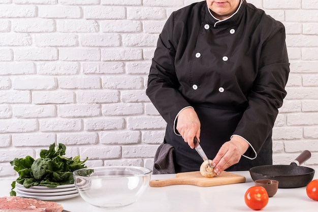 Front view of female chef cutting mushrooms