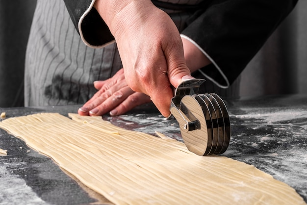 Front view of female chef cutting though into strips