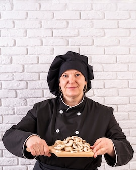 Front view of female chef holding chopped mushrooms