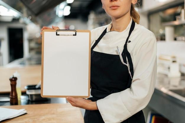 Vista frontale del cuoco unico femminile che tiene appunti