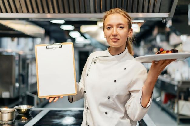 Vista frontale del cuoco unico femminile che tiene piatto e appunti