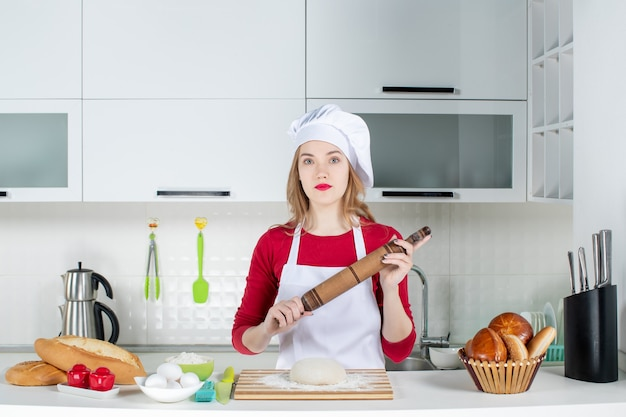 Front view female chef holding rolling pin posing in uniform in the kitchen