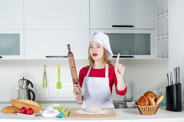 부엌에서 아이디어로 놀라운 롤링 핀을 들고 있는 전면 여성 요리사