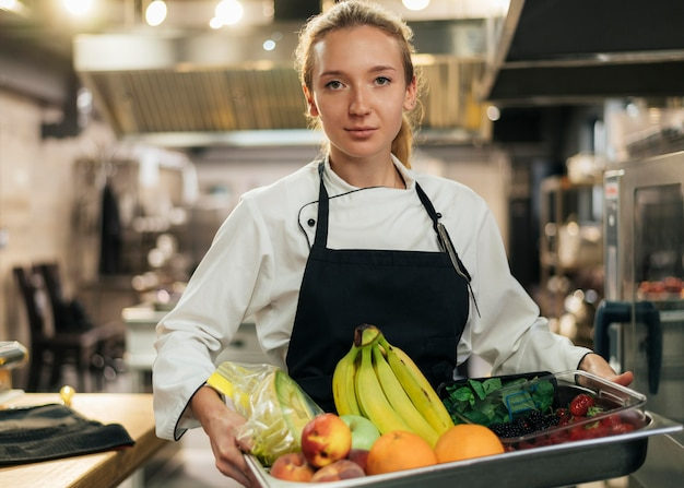 Front view of female chef holding tray of fruit