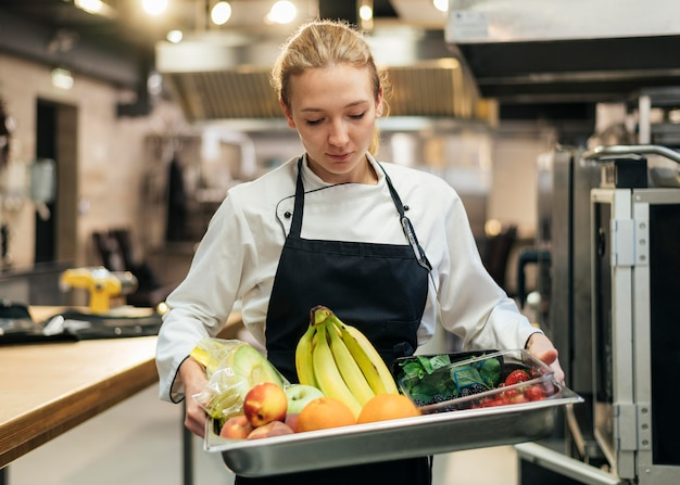 Front view of female chef holding tray with fruit
