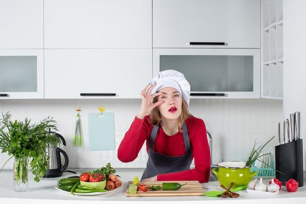 キッチンに立っているクック帽子の正面の女性シェフ