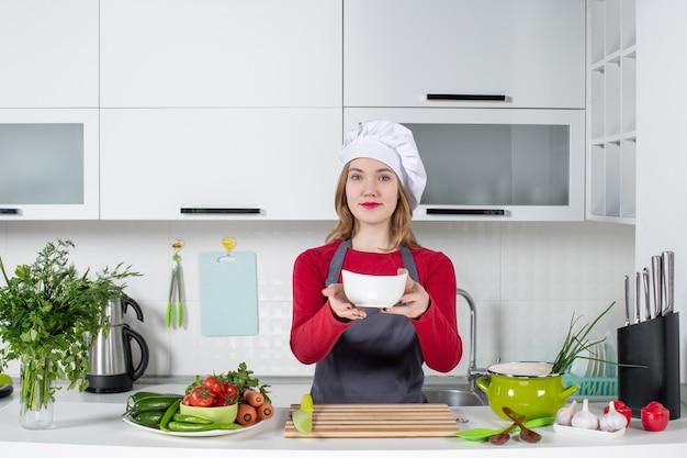 キッチンで均一な保持ボウルに正面図の女性シェフ