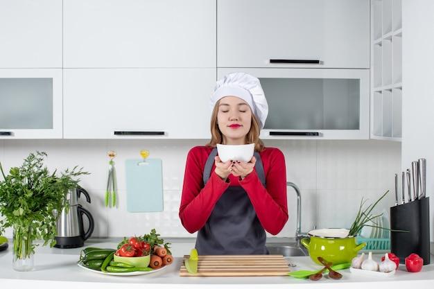 何かのにおいがするボウルを保持している台所のテーブルの後ろに立っている制服を着た女性シェフの正面図