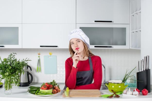 台所のテーブルの後ろに立っている制服を着た女性シェフの正面図