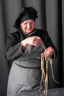 Vista frontale del cuoco unico femminile che produce pasta