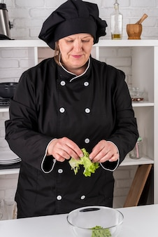 Front view of female chef tearing salad in bowl