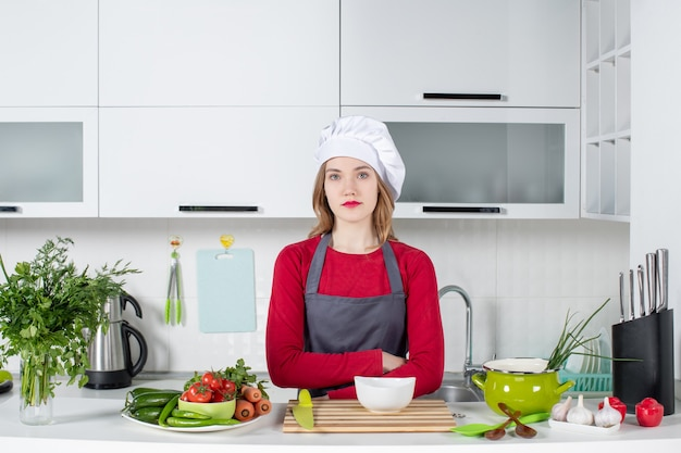 Front view female chef in uniform crossing hands in kitchen