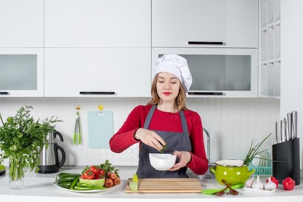 Cuoco unico femminile di vista frontale in ciotola della tenuta dell'uniforme con i verdi