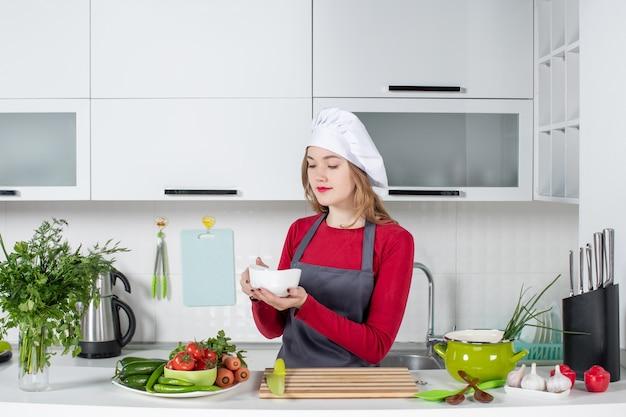 Chef donna vista frontale in uniforme in piedi dietro il tavolo della cucina che tiene la ciotola