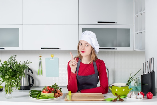 Front view female chef in uniform standing behind kitchen table pointing at finger