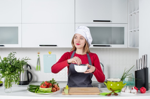 Front view female chef in uniform standing behind kitchen table taking something from bowl