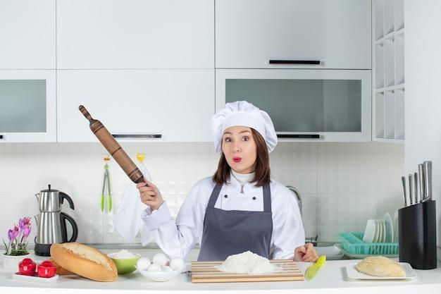 Vista frontale della chef donna in uniforme in piedi dietro il tavolo con gli alimenti del tagliere che tengono il mattarello nella cucina bianca