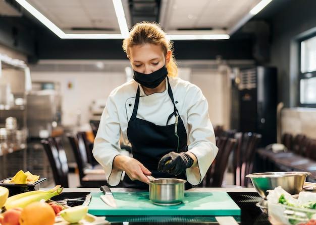 Vista frontale del cuoco unico femminile con la maschera che cucina in cucina