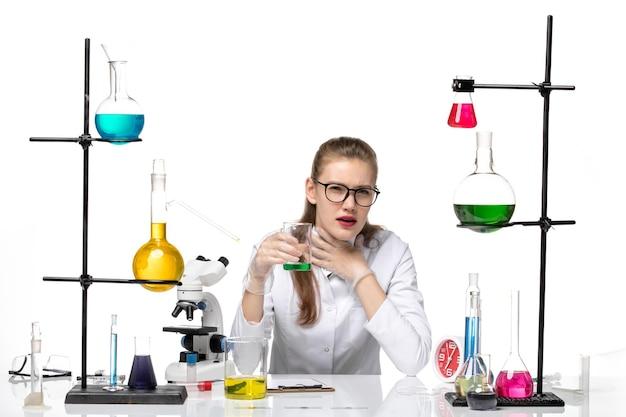白い背景の化学パンデミック健康covidのソリューションのにおいをチェックする医療スーツの正面図女性化学者