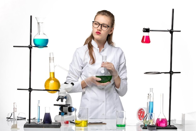 밝은 흰색 배경 화학 전염병 코 비드 바이러스에 녹색 솔루션 플라스크를 들고 의료 소송에서 전면보기 여성 화학자