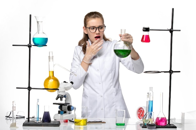 흰색 배경 화학 유행성 코 비드 바이러스에 녹색 솔루션 플라스크를 들고 의료 소송에서 전면보기 여성 화학자