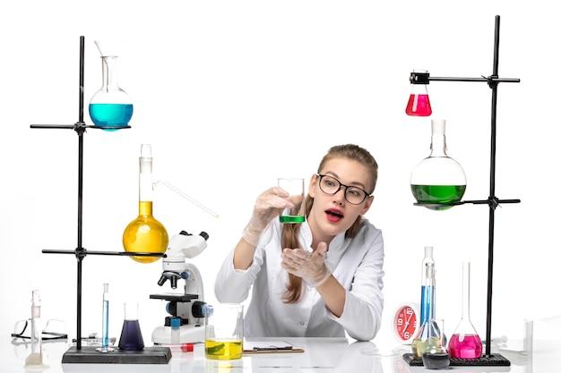 밝은 흰색 배경에 솔루션 플라스크를 들고 의료 소송에서 전면보기 여성 화학자 화학 전염병 건강 covid