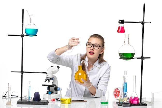 흰색 책상 화학 유행성 covid- 바이러스에 노란색 솔루션 플라스크를 들고 의료 소송에서 전면보기 여성 화학자