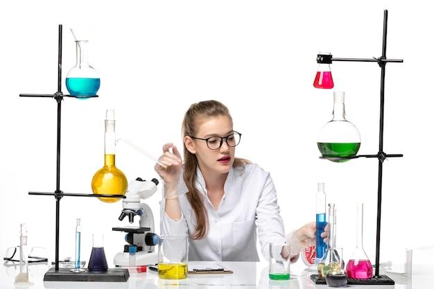 Вид спереди женщина-химик в медицинском костюме, держащая длинную фляжку с синим раствором на белом фоне, пандемия химии, здоровье, covid