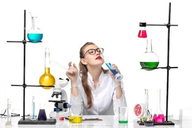 흰색 바닥에 파란색 솔루션으로 긴 플라스크를 들고 의료 소송에서 전면보기 여성 화학자 화학 전염병 건강 covid