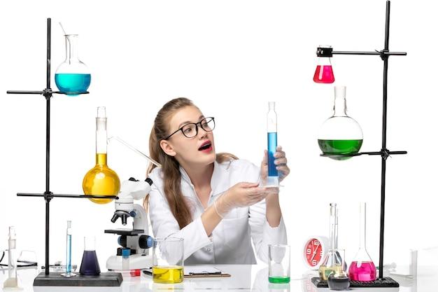 Вид спереди женщина-химик в медицинском костюме, держащая длинную фляжку с раствором на белом фоне, химическая пандемия, здоровье, covid