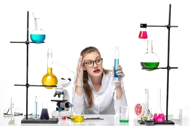 Вид спереди женщина-химик в медицинском костюме, держащая длинную фляжку с раствором на светлом белом фоне, химия, пандемия здоровья, covid