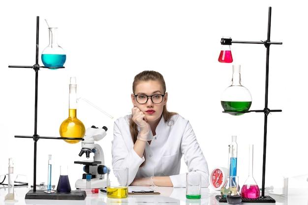 밝은 흰색 배경에 대유행 화학 covid- 바이러스에 대한 솔루션 테이블 앞의 의료 소송에서 전면보기 여성 화학자
