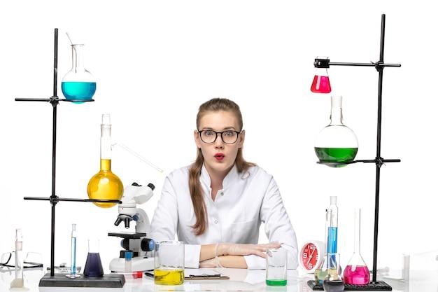 흰색 배경에 대유행 화학 covid- 바이러스에 대한 솔루션 테이블 앞의 의료 소송에서 전면보기 여성 화학자