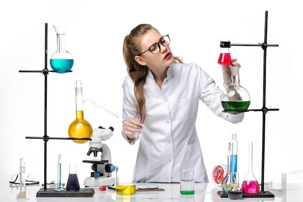 Вид спереди женщина-химик в медицинском костюме в рабочем процессе с растворами на белом фоне химический пандемический вирус covid