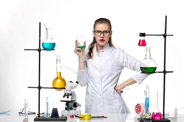 Вид спереди женщина-химик в медицинском костюме в рабочем процессе с растворами на светлом белом фоне химический пандемический вирус covid