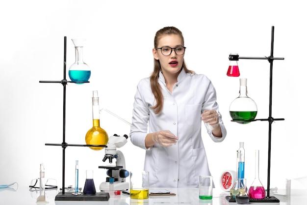 白い背景の化学パンデミックコビッドウイルスの医療スーツの正面図女性化学者