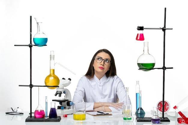 白い背景の実験室ウイルスcovidパンデミック科学の解決策とテーブルの周りに座っている医療スーツの正面図女性化学者